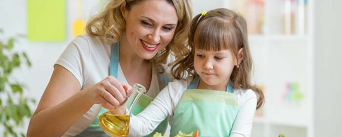 Mother and daughter pouring olivado oil